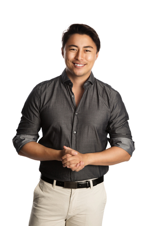 well laid: Relaxed good looking man standing against a white background wearing a grey shirt, smiling looking at camera. Stock Photo