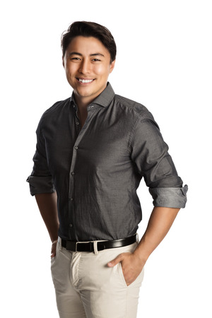 Relaxed good looking man standing against a white background wearing a grey shirt, smiling looking at camera. Stock Photo