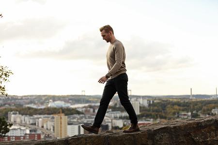 Man draagt een bruine trui en een spijkerbroek, wandelen langs een berg top met de grote cityview achter hem op een zomerse dag. Op zoek weg van de camera. Stockfoto