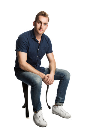 jorobado: Un hombre triste que se sienta en un taburete delante de un fondo blanco, desgastando una camisa azul y los pantalones vaqueros con los zapatos blancos, mirando la cámara.