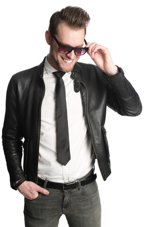 Handsome man in leather jacket, white shirt and sunglasses standing against a white background. Stock Photo
