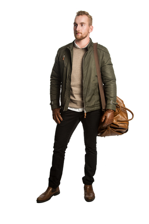 leather bag: Trendy attractive man in his 20s, standing against a white background wearing dark pants, green jacket with brown leather gloves and a leather bag. Looking away from camera.