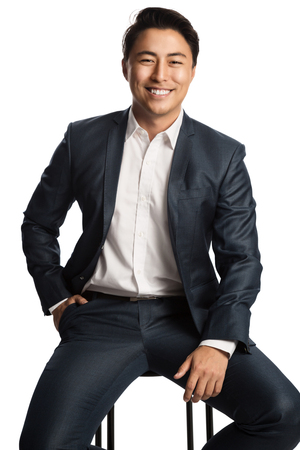 Successful and happy entrepreneur in a blue suit and white shirt, sitting down in front of a white background smiling towards camera.
