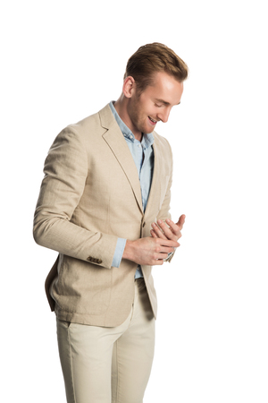 Attractive blonde man standing against a white background wearing a khaki bright suit with a blue shirt, feeling calm and relaxed.
