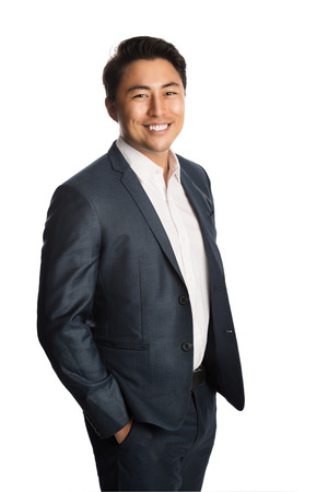 Handsome businessman wearing a blue suit and white shirt, standing with his hands in pocket. White background.