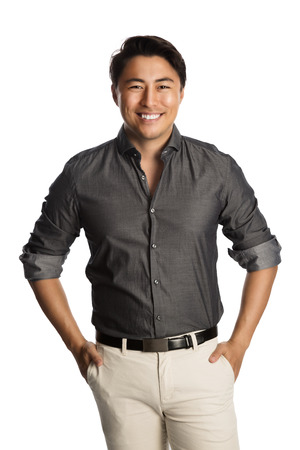 well laid: Cool laid back man wearing a grey shirt with rolled up sleeves and khaki pants, standing with a big smile against a white background. Stock Photo