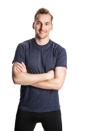tight focus: Blonde man wearing workout clothing standing against a white background staring at camera.