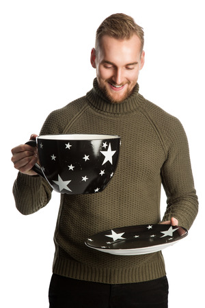 Laughing man wearing a green turtle neck sweater and holding a big oversized mug. Standing against a white background.