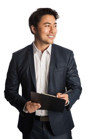 Aantrekkelijke zakenman in een blauw pak en wit overhemd, met een klembord en een pen. Staand tegen een witte achtergrond met een grote brede glimlach.