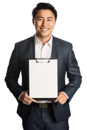 クリップボードとペンを保持している紺のスーツと白いシャツで魅力的な実業家。こぼれるような笑顔で白い背景に立っています。