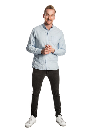 well laid: An attractive man wearing a light blue shirt and dark jeans with a big toothy smile. Standing against a white background.