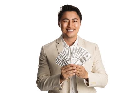 Apuesto hombre de negocios con un traje de color caqui y camisa, de pie sobre un fondo blanco con un gran fan de los billetes de un dólar con una gran sonrisa en su rostro. Foto de archivo - 75539754