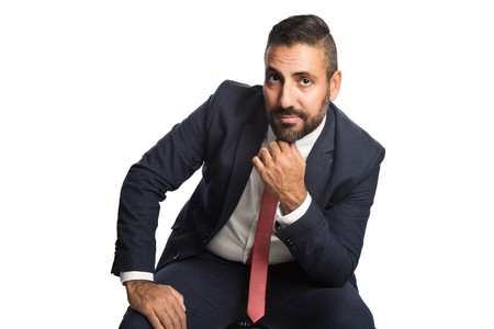 well laid: Handsome businessman in a blue suit and red tie, sitting down in front of a white background with his hand on knee. Stock Photo
