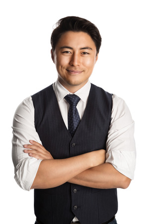 well laid: Fashionable businessman wearing a blue vest, tie and white shirt, standing with a smile against a white background.