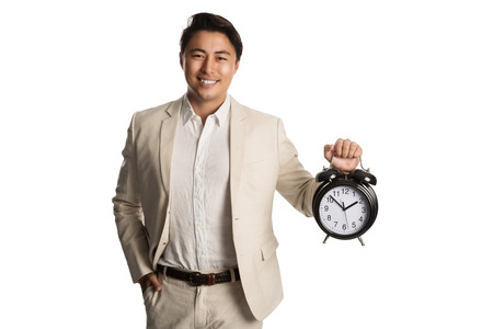 Smiling businessman in a beige suit holding a large clock with a big toothy smile looking at camera. White background.
