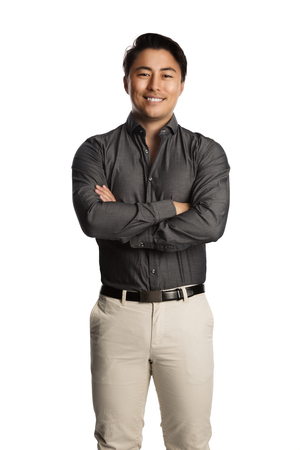 Attractive calm man wearing a grey shirt and beige pants standing against a white background, confident and satisfied. Stock Photo