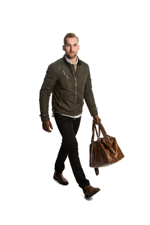 Attractive fashionable man holding a leather bag taking a walk in front of a white background.