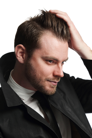 well laid: Portrait of an attractive man holding his hand in his hair looking away from camera, wearing a white shirt and tie with a dark coat.