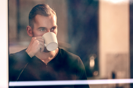 Handsome man drinking from a mug looking out of the window from inside house, wearing a black shirt. Imagens