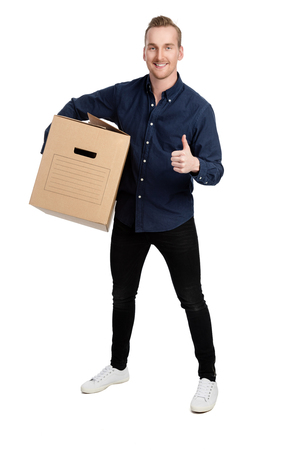 big shirt: Handsome man in blue shirt and jeans, standing against a white background holding a cardboard box with a big smile on his face.