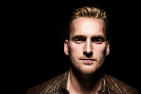 shallow: Handsome blonde man standing against a black background with a simple light above his head, wearing a brown leather jacket and white t-shirt. Stock Photo