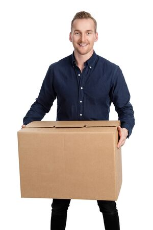 Handsome man in blue shirt and jeans, standing against a white background holding a cardboard box with a big smile on his face.