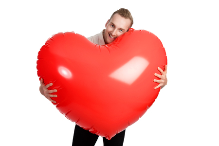 Man standing with a huge oversized heart with a big smile on his face wearing a white shirt. White background.