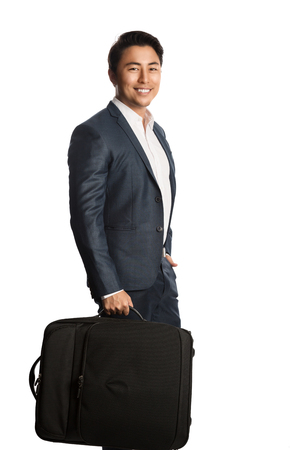travelling salesman: Handsome smiling businessman wearing a blue suit and shirt, standing against a white background holding a traveling bag.