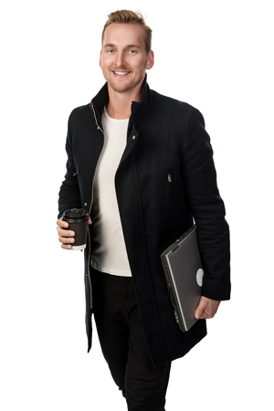 Blonde man in a black coat holding a laptop computer under his arm and a paper mug in his other standing against a white background. Stock Photo