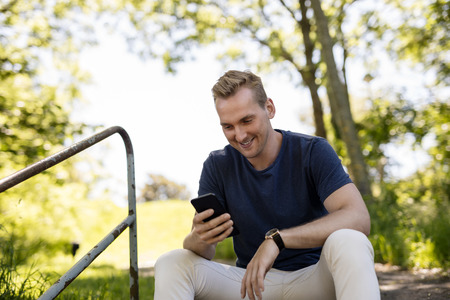 looking for love: Handsome blonde man sitting down outdoors relaxed using his cellphone on a sunny summer day. Stock Photo