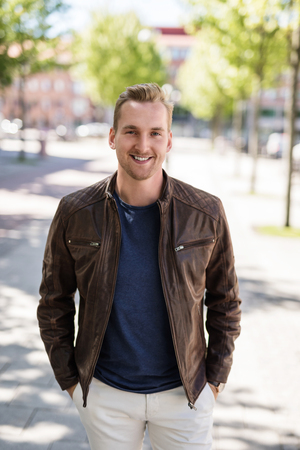 Satisfied man with a smile standing on walkway in the city wearing a brown leather jacket and blue tshirt on a sunny summer day. Stock Photo