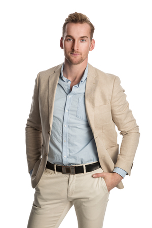 Handsome relaxed businessperson in a beige suit and blue shirt, standing looking at camera against a white background. Stock Photo