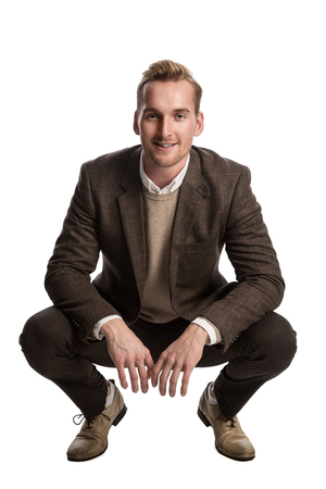 khaki: Attractive businessman in a brown suit and beige pullover shirt, standing against a white background smiling.