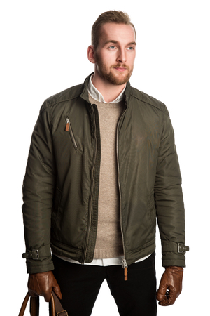 Trendy attractive man in his 20s, standing against a white background wearing dark pants, green jacket with brown leather gloves and a leather bag. Looking away from camera.