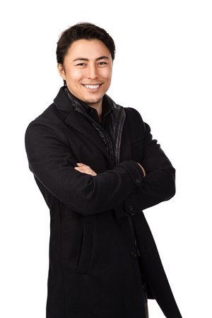 Handsome man wearing a warm black jacket, looking at camera with a big smile on his face. Standing against a white background. Stock Photo