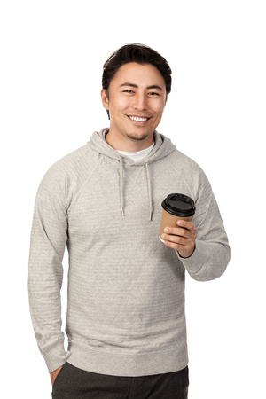 An attractive man in his 20s standing against a white background wearing a grey hood shirt smiling and holding a take-away cup coffee cup, looking at camera. Stockfoto