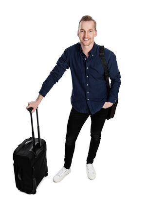 Smiling blonde man wearing a blue shirt and black jeans with sneaker, holding a luggage bag and computer bag smiling towards camera. White background.