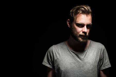 Portrait of a bearded man with an intense look standing in a dark room against a black background.
