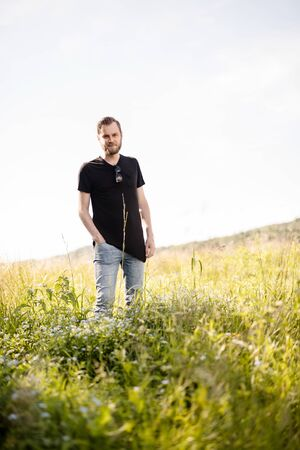 Laid back bearded man wearing a black shirt, standing outdoors on a sunny summer day looking at camera with a smile on his face. Stok Fotoğraf