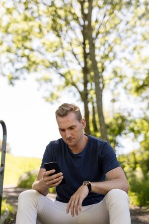 Handsome blonde man sitting down outdoors relaxed using his cellphone on a sunny summer day. 스톡 콘텐츠