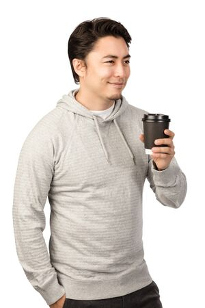 An attractive man in his 20s standing against a white background wearing a grey hood shirt smiling and holding a take-away cup coffee cup, looking away from camera.