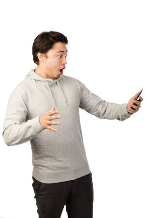 Handsome man in grey hoodie looking shocked at his mobile phone with mouth wide open. White background.