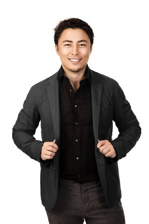 Handsome young entrepreneur with a smile standing against a white background wearing a grey suit and black shirt.