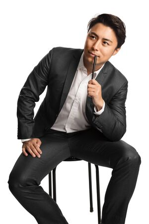 Creative businessman in a blue suit and white shirt, holding a pen thinking. White background.