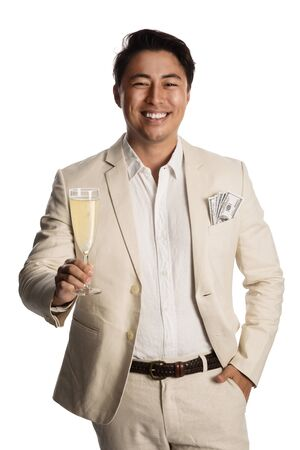 Handsome smiling man wearing a bright suit and white shirt, holding a champagne glass with money in his pocket looking at camera. White background.