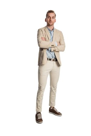 Handsome relaxed businessperson in a beige suit and blue shirt, standing looking at camera against a white background. Stok Fotoğraf