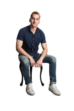 A smirking man sitting down on a stool in front of a white background, wearing a blue shirt and jeans with white shoes, looking at camera. 스톡 콘텐츠