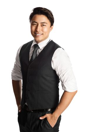 Image of a young handsome Asian male business man looking confident wearing a black vest, tie and white collared shirt with both hands in his pocket smiling directly at the camera.