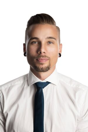 Handsome and bearded Scandinavian corporate man wearing a blue tie and white shirt looking pensive at the camera.