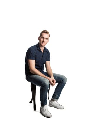 A picture of a European male sitting casually on a stool loving his weekend wearing casual clothes. Standard-Bild